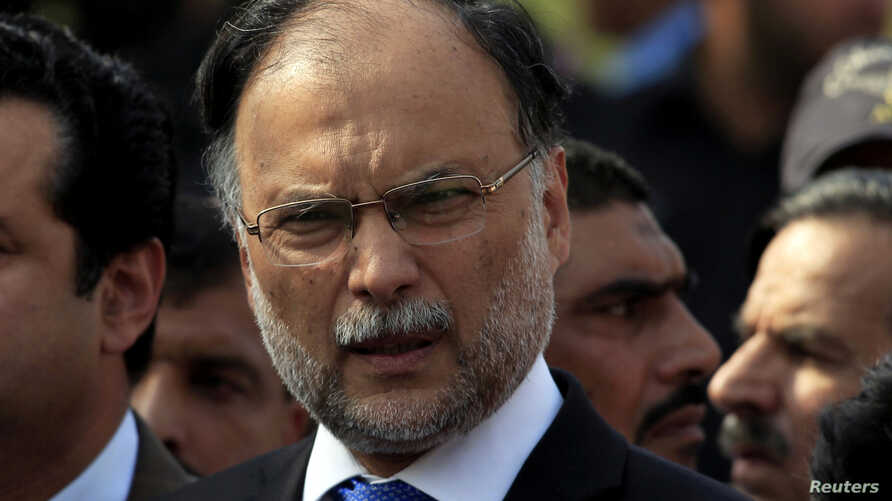 FILE - Pakistan's Interior Minister Ahsan Iqbal speaks to media outside the accountability court in Islamabad, Pakistan, Oct. 2, 2017.