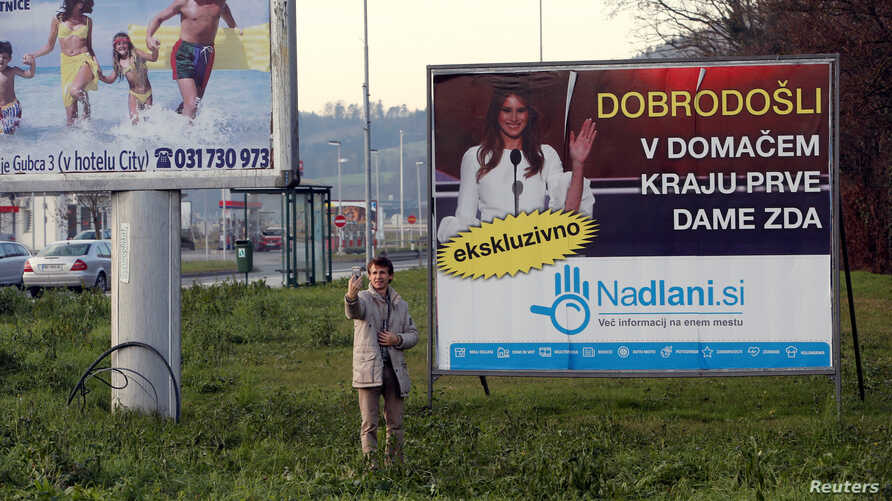 A man takes a selfie in front of placard with a picture of Melania Trump in her hometown Sevnica, Slovenia, Dec. 1, 2016. Banner reads 'Welcome in hometown of first lady of U.S.'