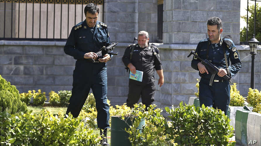 FILE - Police officers patrol Iran's parliament building after an assault by several attackers that was claimed by the Islamic State group, in Tehran, Iran, June 7, 2017. Gunmen and suicide bombers attacked Iran's parliament and the shrine of its rev