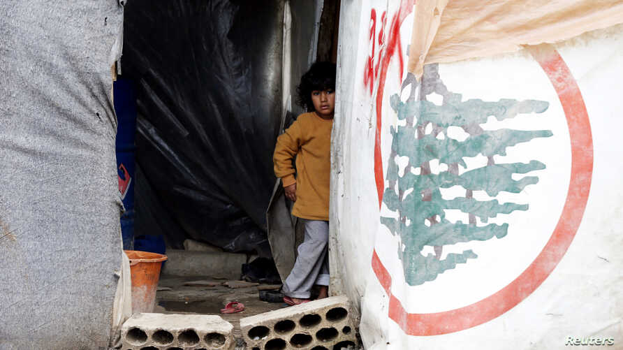 A Syrian refugee girl looks out from a tent at a makeshift settlement in Bar Elias in Lebanon's Bekaa Valley Jan. 5, 2015.