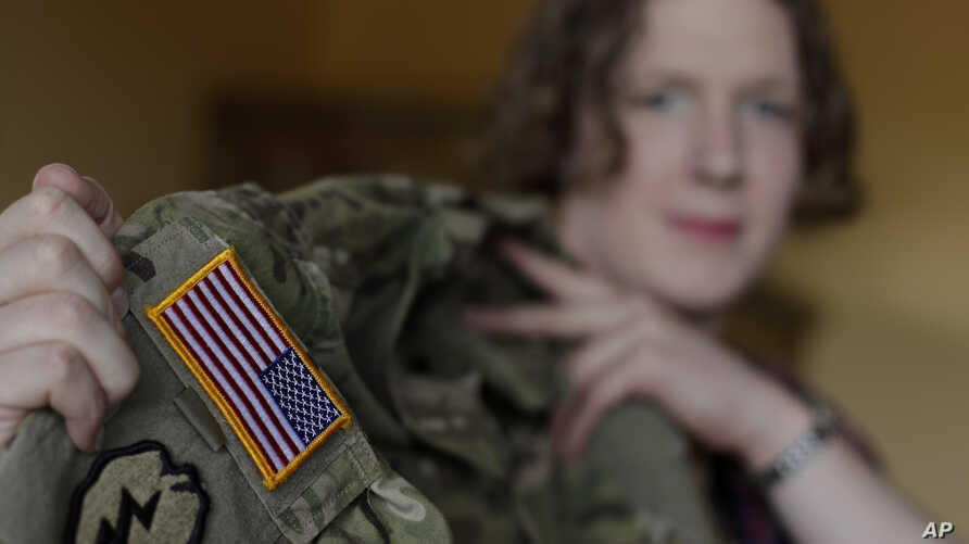 Transgender U.S. army captain Jennifer Sims lifts her uniform during an interview with The Associated Press in Beratzhausen near Regensburg, Germany, July 29, 2017.