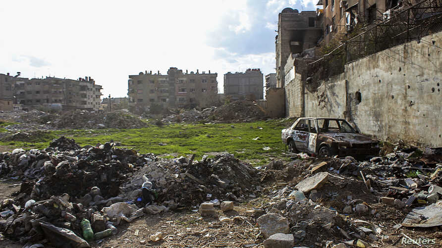 A damaged car lies amongst debris on one of the battlefronts in Jobar, a suburb of Damascus, Syria, Feb. 22, 2014.