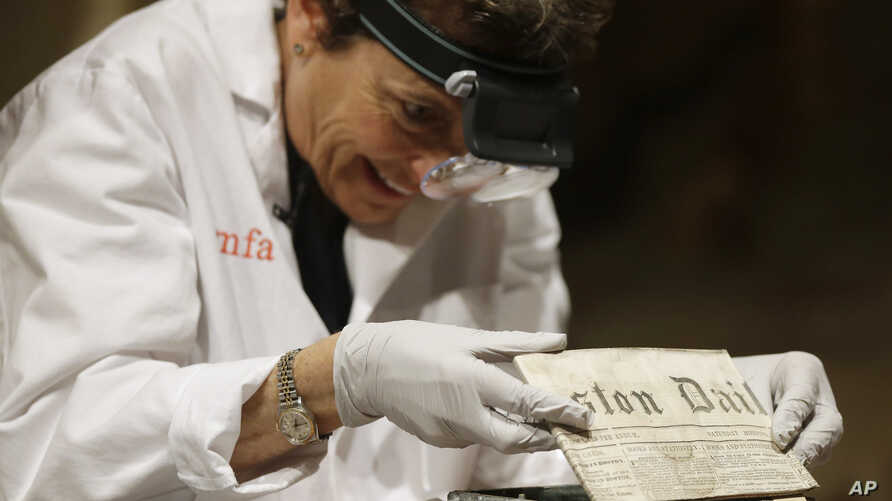 Pam Hatchfield, head of objects conservation at the Museum of Fine Arts in Boston, removes a folded 19th-century newspaper from a time capsule at the museum, Jan. 6, 2015.