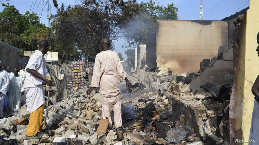FILE - Residents watch as two men walk amidst rubble after Boko Haram militants raided the town of Benisheik, west of Borno State capital Maiduguri, Nigeria, Sept. 19, 2013.