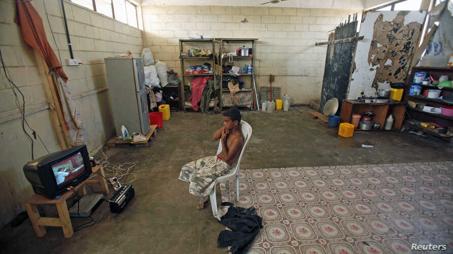 File- A boy watches TV in his family's shelter at a school in the southern Yemeni port city of Aden.