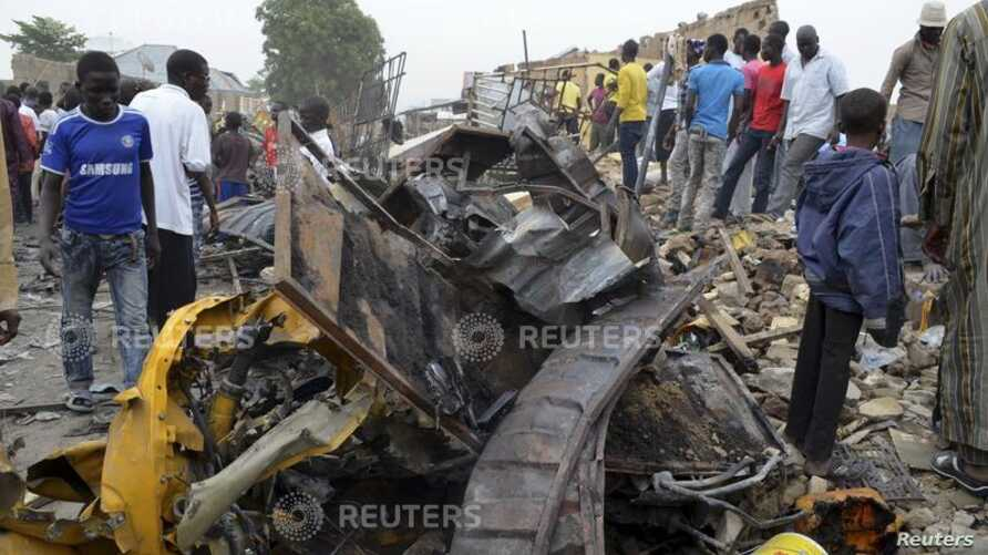 People look at damage in a market area after a bomb explosion in Ajilari-Gomari near the city's airport, Maiduguri, Borno State March 2, 2014.