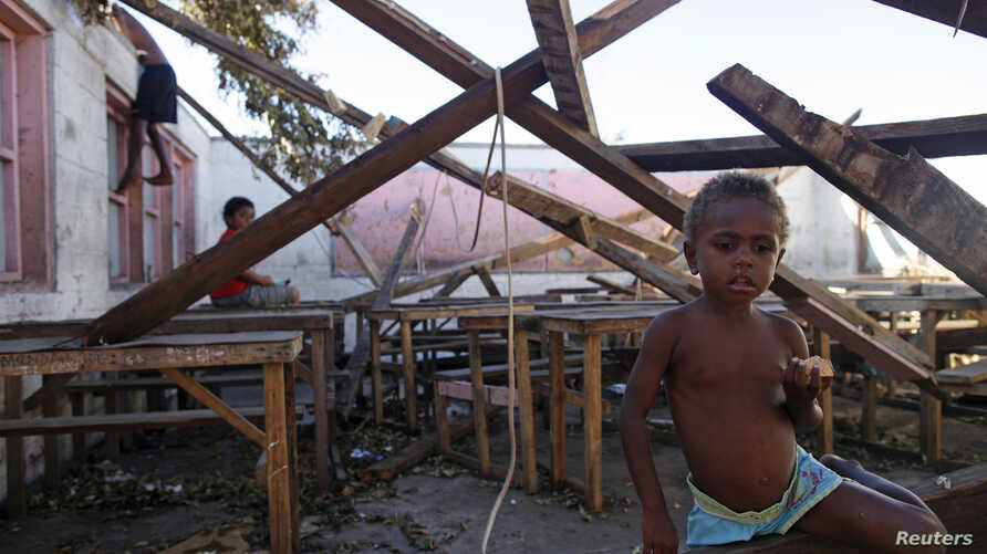 FILE - Children play in a destroyed school classroom in Tanna, March 18, 2015, after a powerful storm wiped out crops and destroyed fishing fleets, raising the risk of hunger and disease.