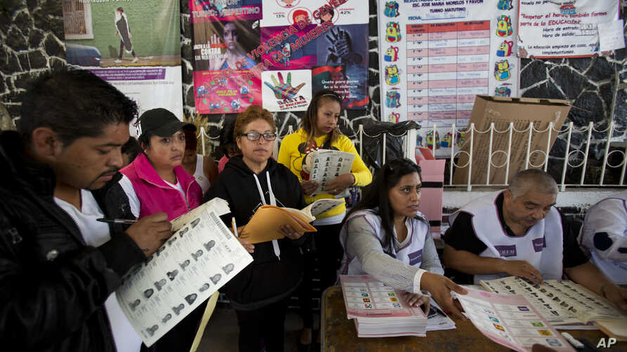 An election worker hands a ballot to a voter as observers from political parties mark off each voter from copies of the rolls in Chimalhuacan, Mexico state,  June 4, 2017.