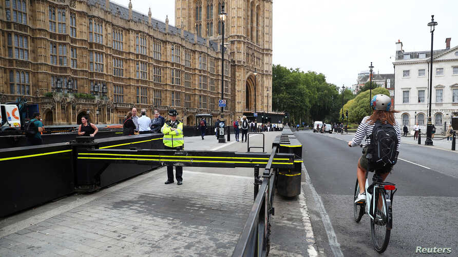 A cyclist passes a police officer standing at the vehicle barrier to the Houses of Parliament where a car crashed after knocking down cyclists and pedestrians the day before in Westminster, London, England, Aug. 15, 2018.