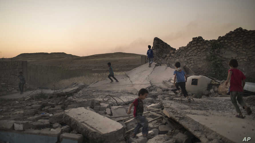 FILE - Children play on debris in a neighborhood retaken by Iraqi security forces during fighting against Islamic State militants in West Mosul, Iraq, June 25, 2017.