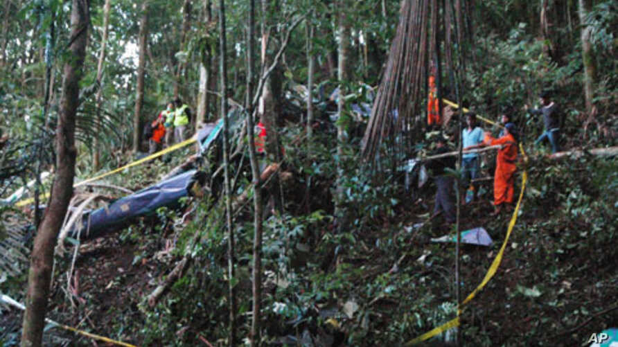 A rescue team examines the wreckage of a helicopter which crashed in Gunung Dua Sudara Bitung, in Indonesia's north Sulawesi province, August 4, 2011