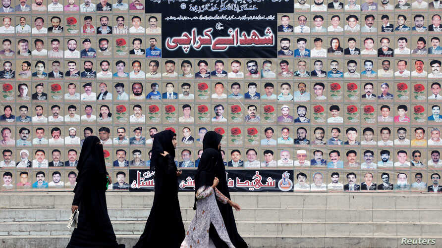Shiite Muslim women walk past a wall with portraits of the deceased, who were killed in a bombing in a residential area in March 2013, during the Shiite Youm Ali procession in Karachi, Pakistan June 27, 2016.
