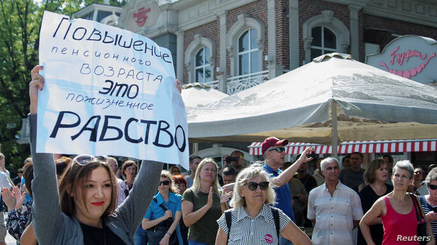 """People attend a rally against planned increases to the nationwide pension age in Krasnodar, Russia, Sept. 9, 2018. The poster reads: """"Pension age increase is a lifetime slavery."""""""