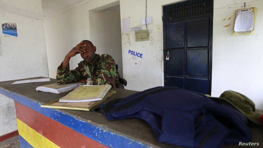 A policeman sits near the scene where his colleague was killed during an attack by gunmen who raided the police station in Gamba, Kenya, July 6, 2014.