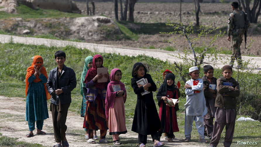 Afghan children hold the holy Koran as they go to a madrasa (religious school) in Dand Ghori district in Baghlan province, Afghanistan, March 15, 2016.