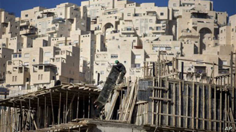 A construction worker works on a new housing unit in the east Jerusalem neighborhood of Har Homa, 08 Dec 2010