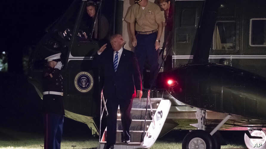 President Donald Trump salutes as he steps off of Marine One on this return to the White House in Washington, Sunday, Aug. 20, 2017.