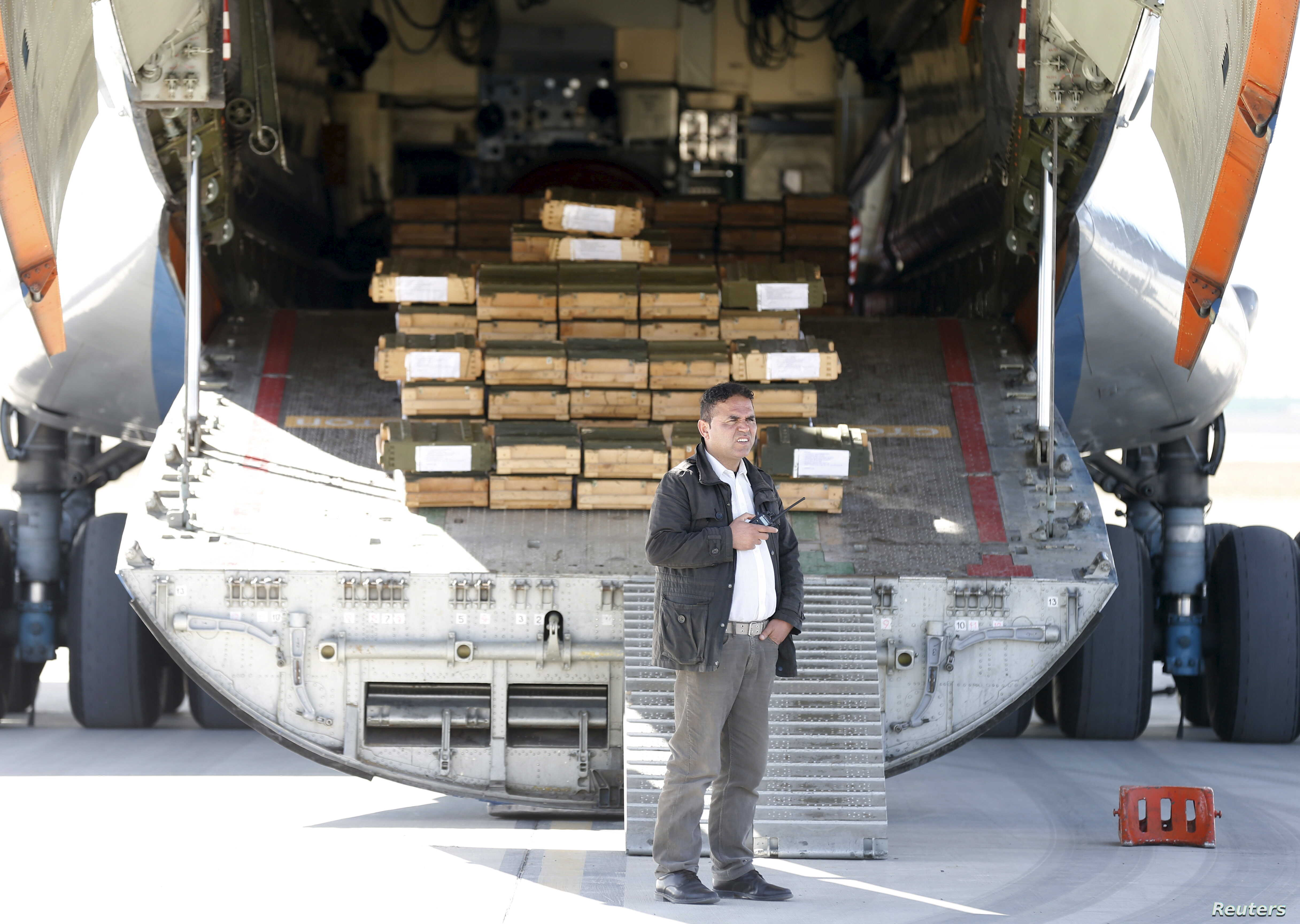 An Afghan security officer stands next to boxes of ammunition inside a Russian aircraft at the International Kabul Airport, Afghanistan, Feb. 24, 2016.