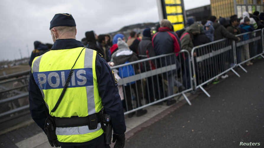 FILE - A police officer keeps guard as migrants arrive at Hyllie station outside Malmo, Sweden.