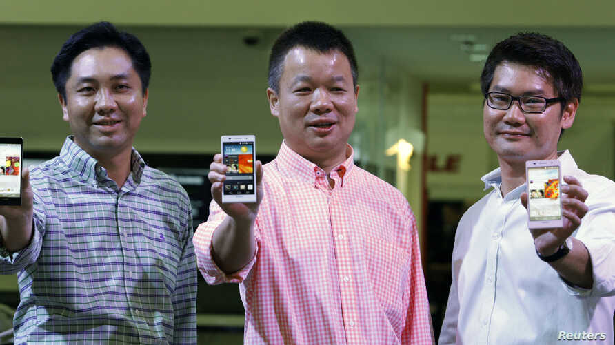 Huawei's Singapore CEO Zhou Bin (L-R), David Wei, President of Huawei South Pacific and Lim Chee Siong Chief Marketing Officer, Huawei South Pacific, show the new Huawei Ascend P6 Android-based smartphones during their launch at CommunicAsia communic