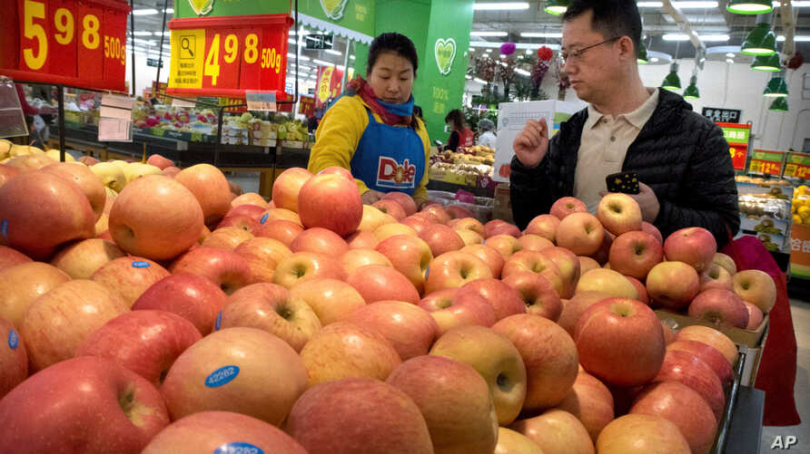 FILE -  a woman wearing a uniform with the logo of an American produce company helps a customer shop for apples a supermarket in Beijing.