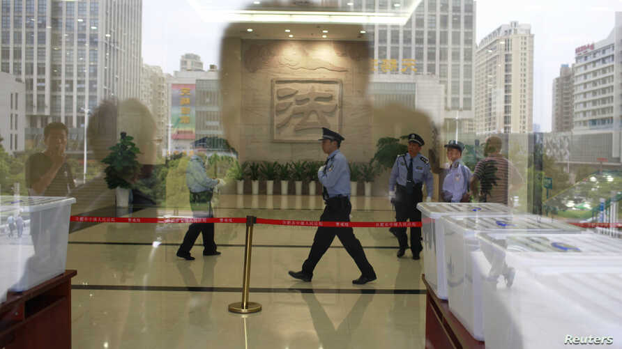 Police officers walk inside Hefei Intermediate People's Court, where the Gu Kailai trial will be held on Thursday, in Hefei, Anhui Province August 8, 2012. (File photo)