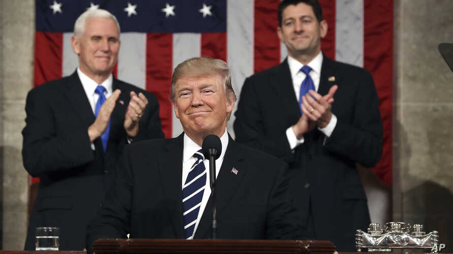 President Donald Trump, flanked by Vice President Mike Pence, left, and House Speaker Paul Ryan arrives on Capitol Hill in Washington for his address to a joint session of Congress, Feb. 28, 2017.
