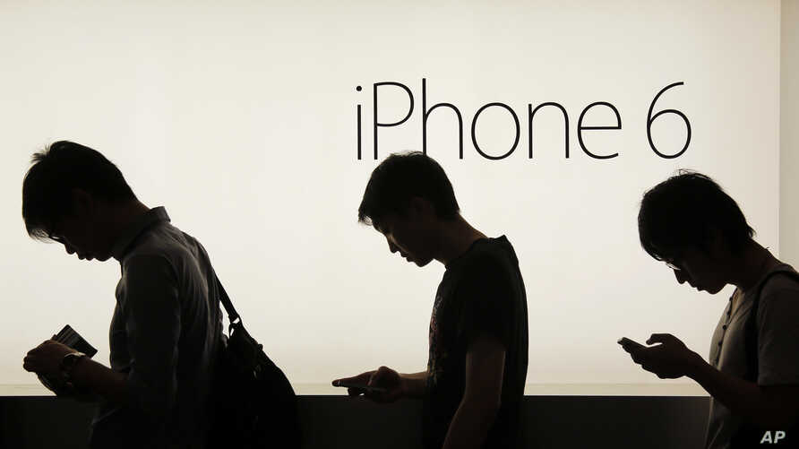 File - People wait to buy the Apple iPhone 6 and 6 Plus devices outside an Apple store in Hong Kong, Sept. 19, 2014.