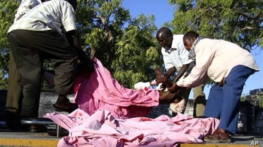 A body is loaded onto the flatbed of a truck by relatives at Medina hospital, in Mogadishu, Somalia, Jan. 31, 2011.