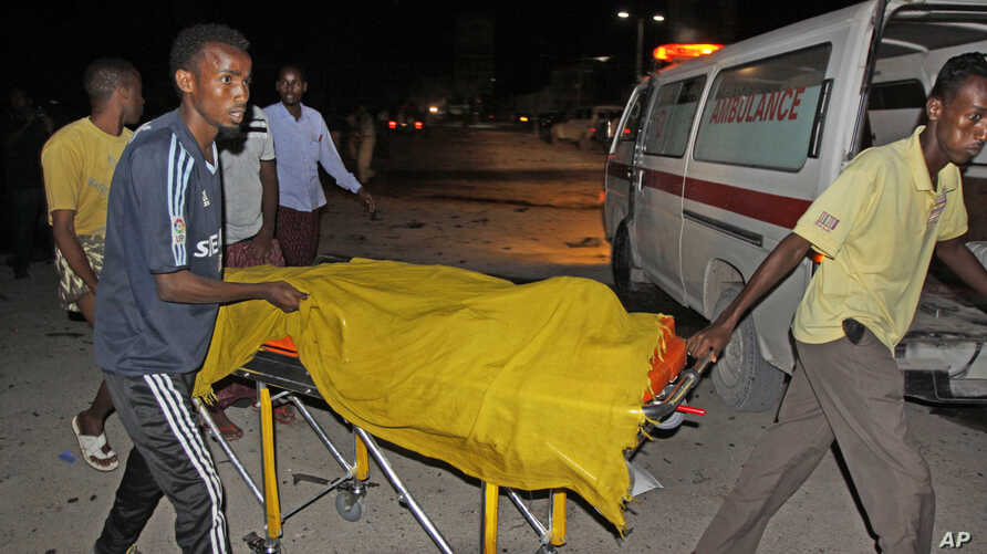 Rescuers remove a dead body from the scene of a car bomb attack close to the presidential palace in the capital Mogadishu, Somalia, Oct. 15, 2014.