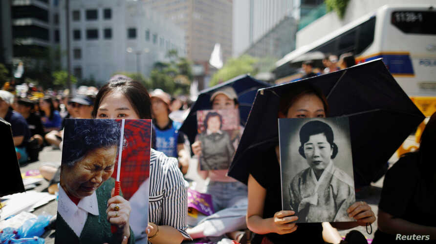 "FILE - Women hold portraits of deceased former South Korean ""comfort women"" during a weekly anti-Japan rally in Seoul, South Korea, Aug. 15, 2018."
