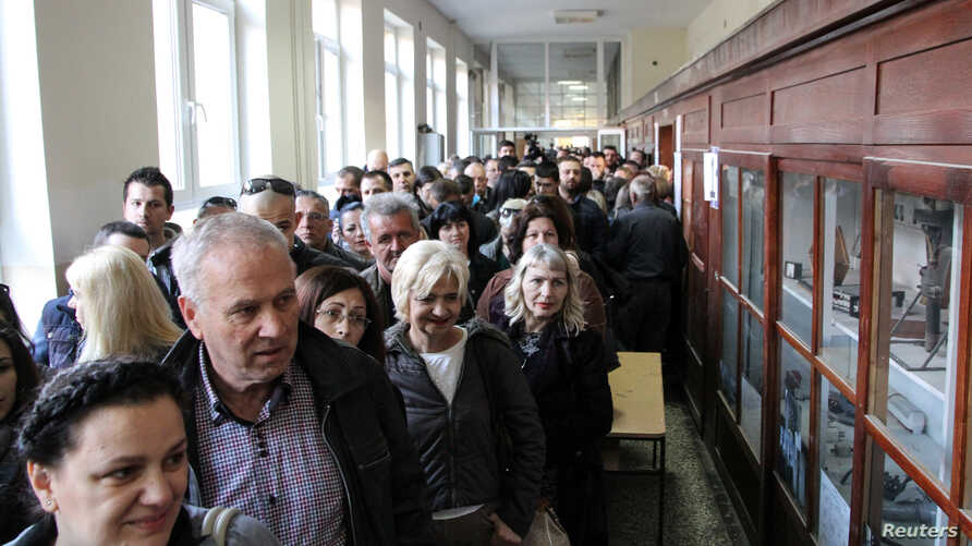 People wait in line to cast their votes at a polling station during Serbian presidential election in the ethnically divided town of Mitrovica, Kosovo, April 2, 2017. Kosovars go to the polls Sunday to choose a new parliament.