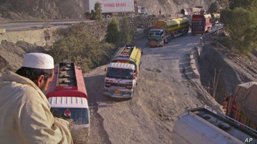 A driver sits overlooking trucks parked along the road, including those carrying supplies to NATO forces in Afghanistan, near Pakistan's Torkham border, after it was shut down to traffic November 26, 2011.