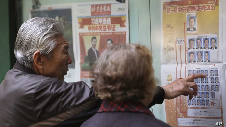 A Chinese couple look at a newspaper reporting on new General Secretary of Communist Party of China Xi Jinping and other members of the party leadership in Beijing, China,  Nov. 16, 2012.