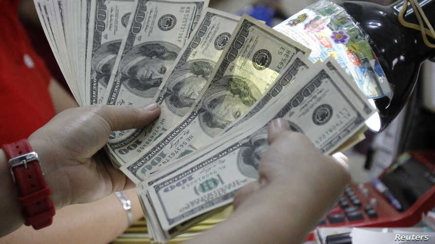 A worker counts U.S. dollar bills, which are being exchanged for Philippine Pesos, inside a money changer in Manila April 1, 2013.