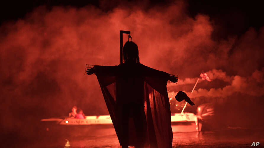 """People on a boat hold flares as they sail behind the effigy of Judas during the revival of the old Easter tradition of the """"burning of the Judas"""", in the port town of Ermioni, in the Peloponnese peninsula, southwest of Athens, April 8, 2018."""