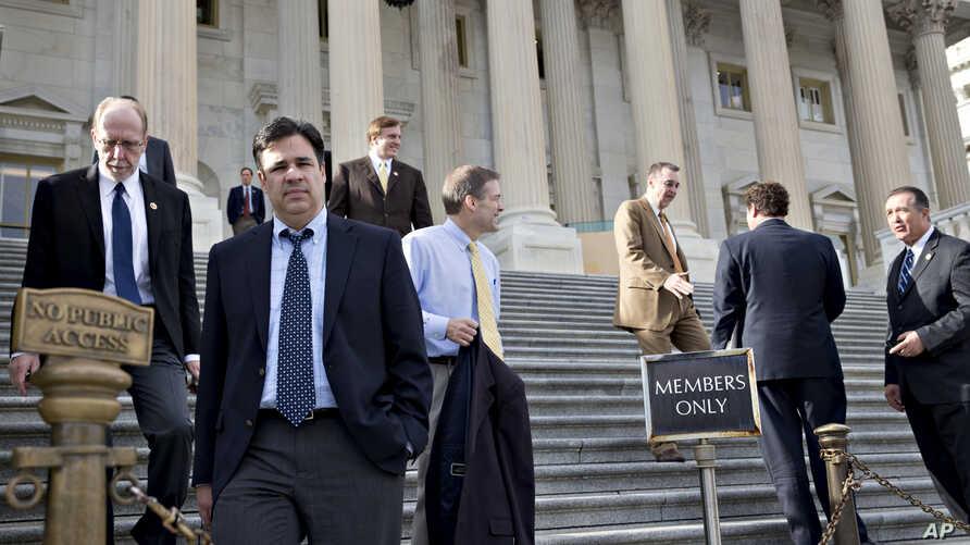 """Rep. Raul Labrador (2nd from L) and members of the House of Representatives leave after the Republican-controlled House voted to let insurance companies sell individual health coverage to all comers, even if it falls short of required standards in """"O"""