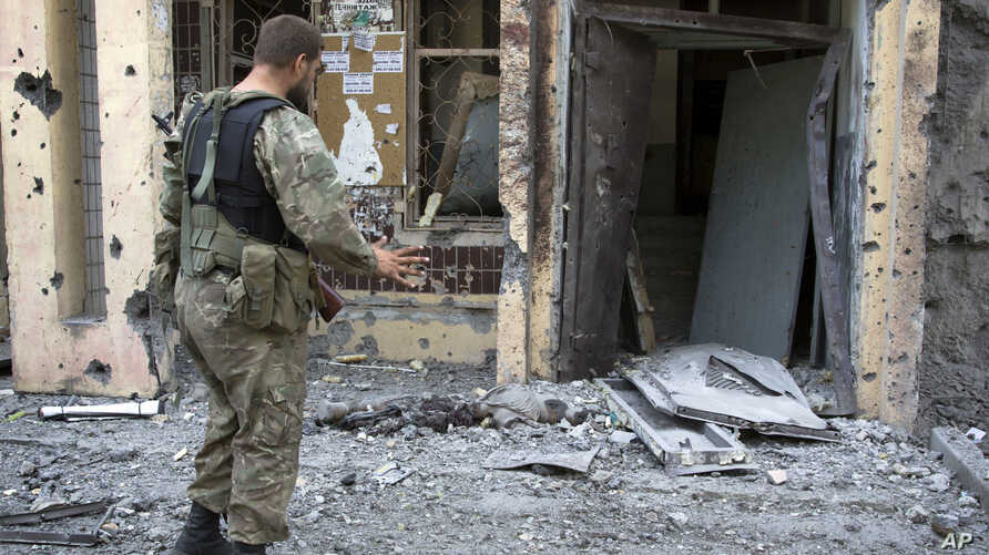 A pro-Russian fighter gestures near a body of a community service worker who was killed during the shelling outside a residential apartment house in Donetsk, eastern Ukraine, July 29, 2014.