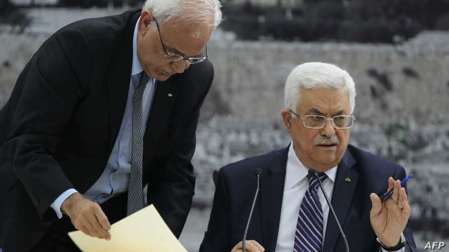 Palestinian president Mahmud Abbas (R) gestures as he signs a request to join 15 United Nations agencies at his headquarters in the West Bank city of Ramallah on April 1, 2014.
