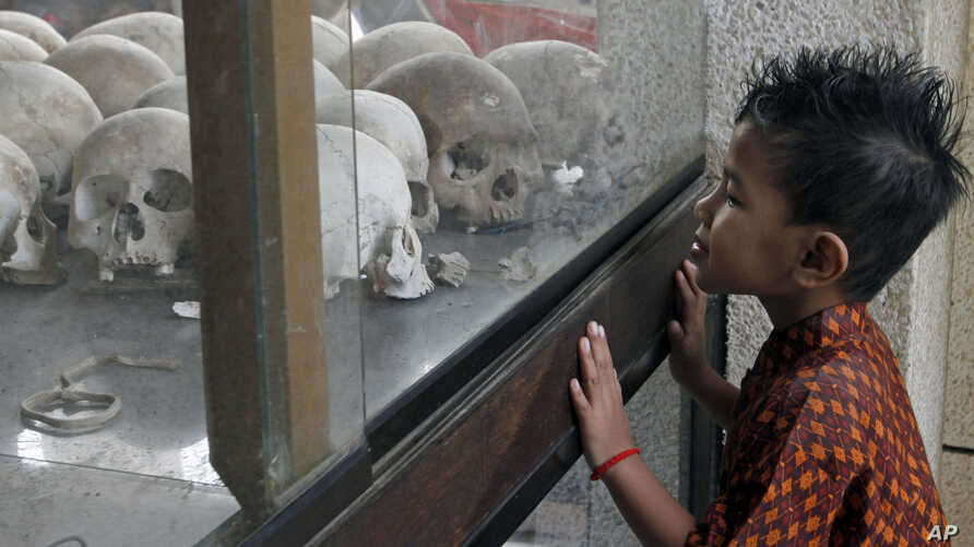A boy looks at a pile of skulls in a stupa at Choeung Ek memorial on the outskirts of Phnom Penh, Cambodia,  April 17, 2014.