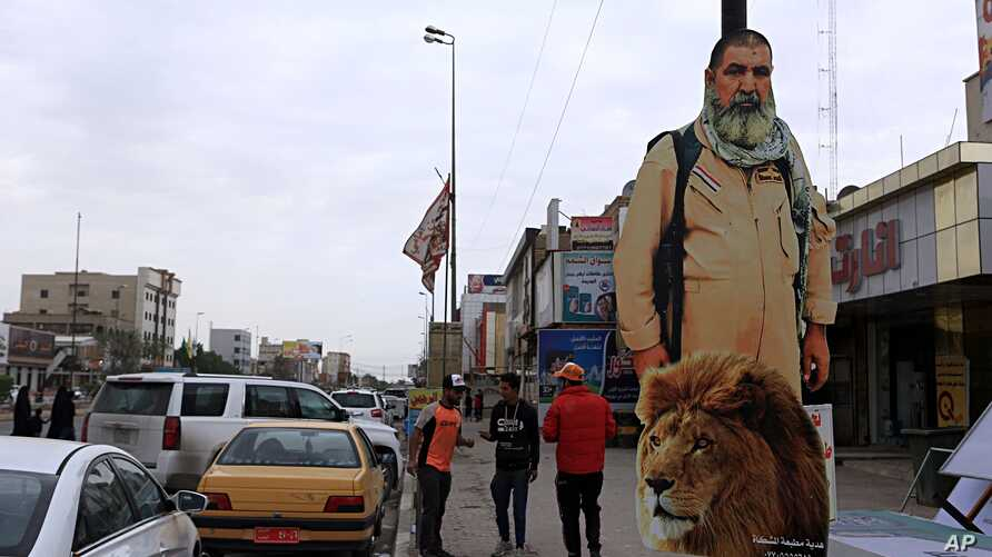 FILE - People pass by a poster of Ali Jayad al-Salhi, 65, a volunteer with Popular Mobilization Forces killed fighting Islamic State militants, in Basra, 340 miles (550 kilometers) southeast of Baghdad, Iraq, Nov. 26, 2017.