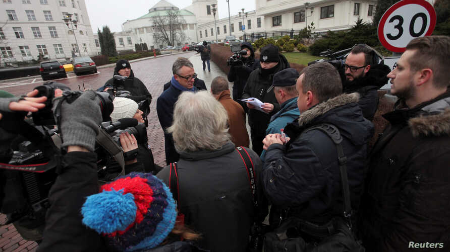 Media representatives wait to enter for a meeting with the Speaker of Senate during the fourth day of a protest in front of the Parliament building in Warsaw, Poland, Dec. 19, 2016.