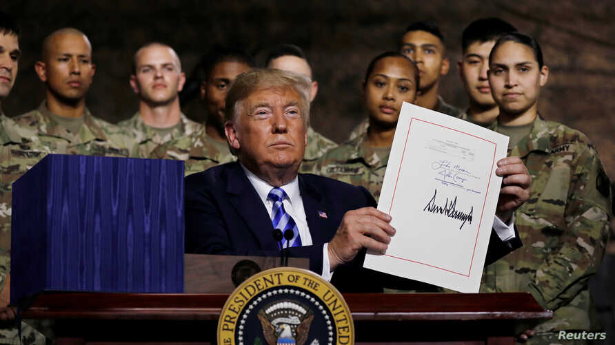 U.S. President Donald Trump holds up the National Defense Authorization Act after signing it in front of soldiers from the U.S. Army's 10th Mountain Division at Fort Drum, New York, Aug. 13, 2018.