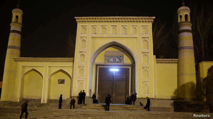 FILE - Men stand outside the Id Kah Mosque before morning prayers in Kashgar, Xinjiang Uighur Autonomous Region, China, March 23, 2017.