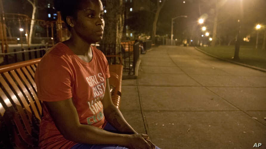FILE - In this June 23, 2015 photo, refusing to return to a shelter following a confrontation with another resident, Candie Hailey sits on a bench near the housing complex where she once lived, pondering where she will spend the night, in New York.