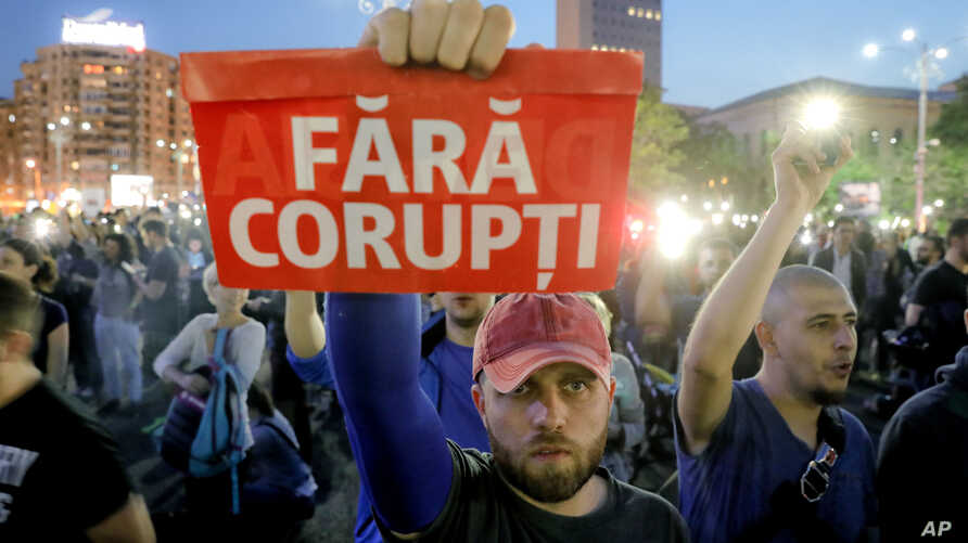 """A man holds a poster that reads """"Without Corruption"""" during a protest in Bucharest, Romania, May 3, 2017. Over one thousand people gathered outside government offices after a parliamentary committee approved a draft measure that would grant amnesty t..."""
