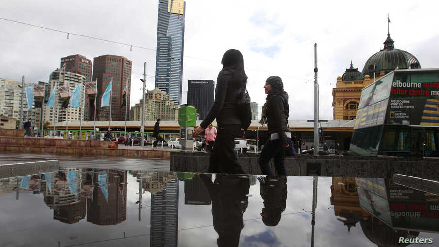FILE - Office workers walk through Federation Square in Melbourne, May 11, 2011. Police say suspected terrorists now under arrest had planned to attack the square and other targets.
