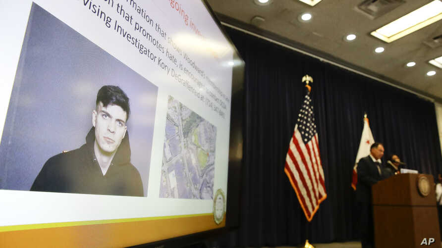The image of Samuel Woodward is displayed as Orange County District Attorney Tony Rackauckas, right, speaks during a news conference, Aug. 2, 2018, in Santa Ana, Calif. Rackauckas, said they will file a hate crime sentencing enhancement against Samue