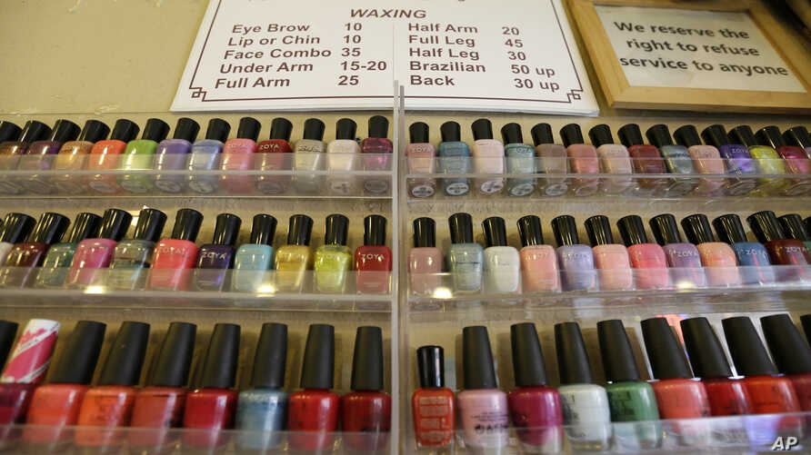 FILE - A wall rack is filled with polishes, Nov. 30, 2016, in Alameda, Calif. A group of Vietnamese-American salon owners in Louisiana accused the state of racial bias and received a $100,000 settlement.