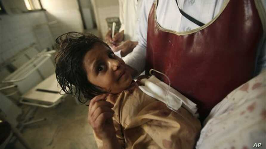 A member of the hospital staff carries a child injured in an attack at a local hospital in Peshawar, Pakistan, September 13, 2011.